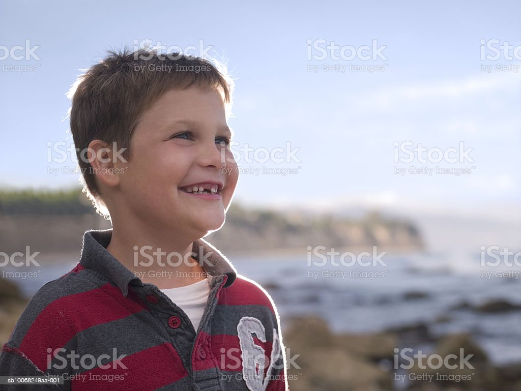 Gap-toothed boy (6-7) smiling by sea royalty-free stock photo
