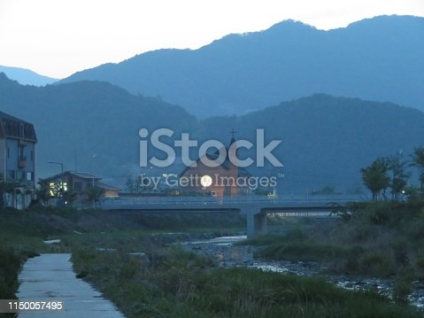 Pastoral twilight landscape featuring a small church with a glowing round window overlooking a creek in Gapyeong, Korea