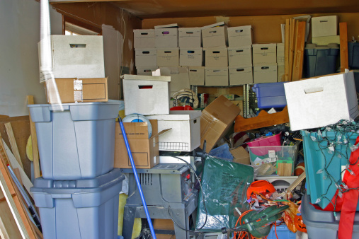 Garage with clutter and storage boxes.