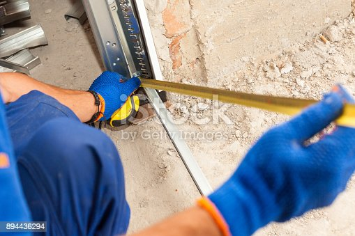istock Garage Door Installation. Worker use a ruler to verify correct installation of metal profile 894436294