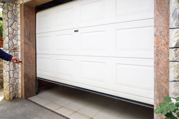 Garage door Garage door PVC. Hand use remote controller for closing and opening garage door automatic stock pictures, royalty-free photos & images