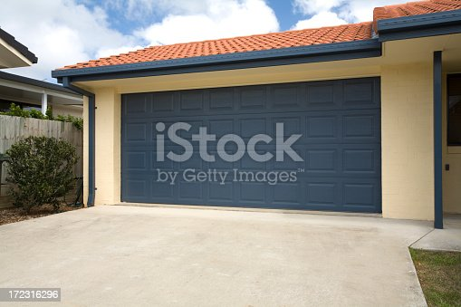 A blue double garage door on a brand new home.