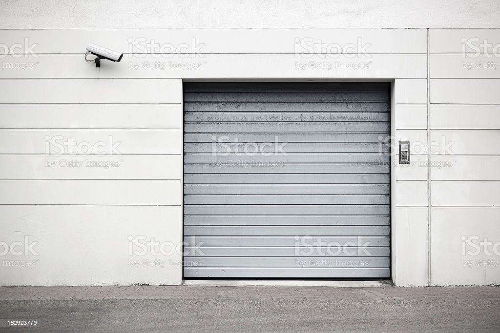 Garage door in building with security equipment.