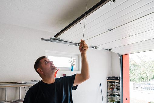 man opens pvc garage door manually