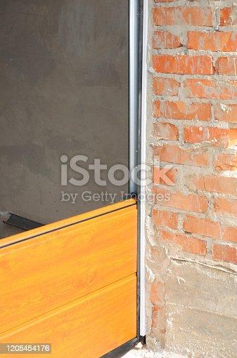istock Garage door replacement, garage door repairing. 1205454176
