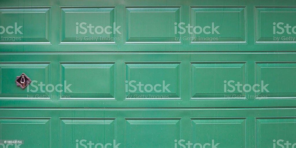 Metal door garage green in color with lock.