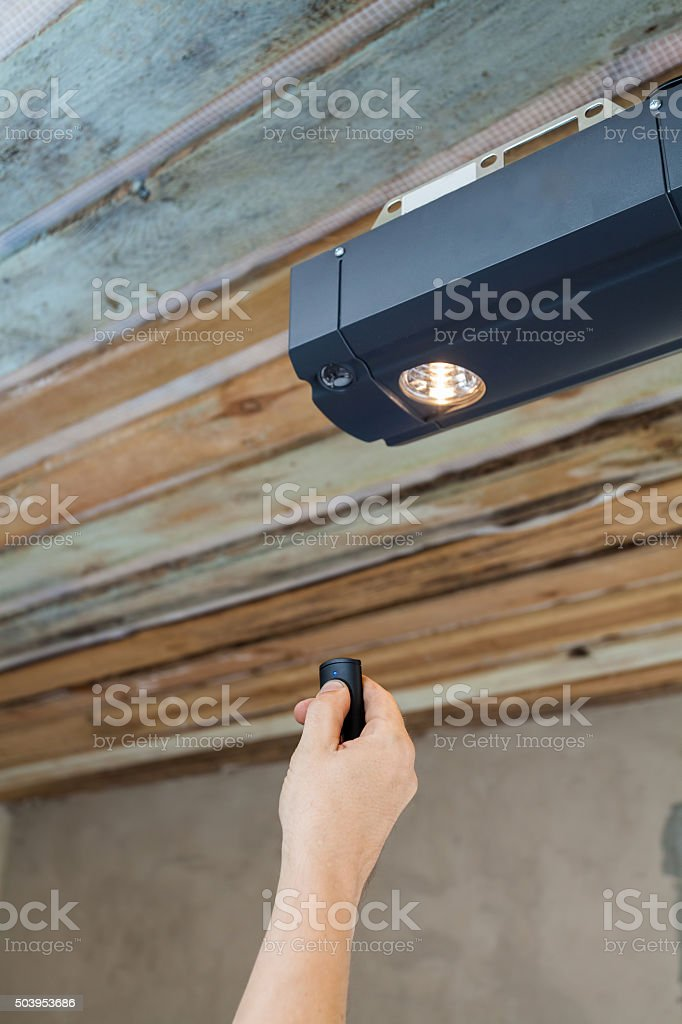 Garage doors installation. Contractor programming a mechanical garage door opener stock photo