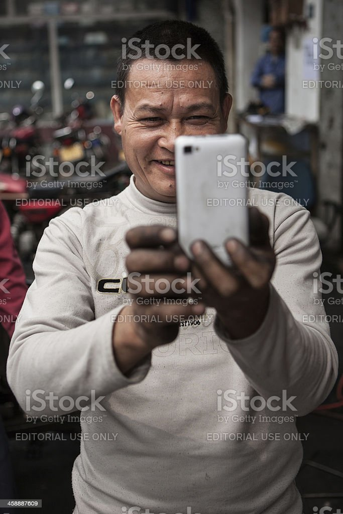 Garage mechanic takes a picture with his smartphone in China stock photo