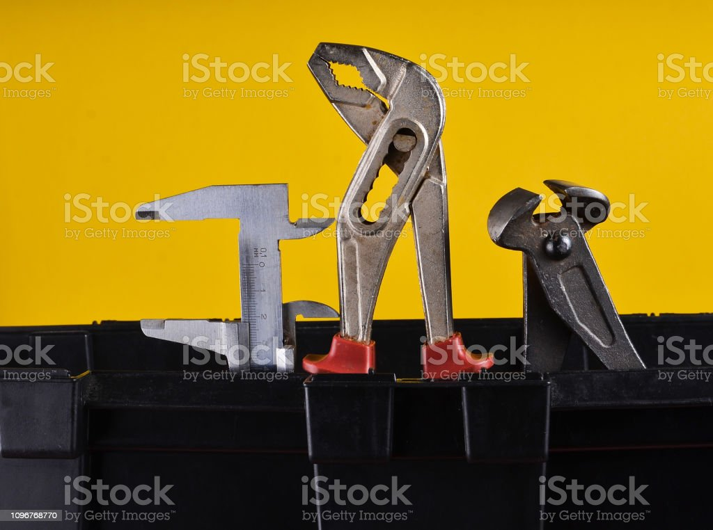 Garage plastic tool box with working tools isolated on a yellow....