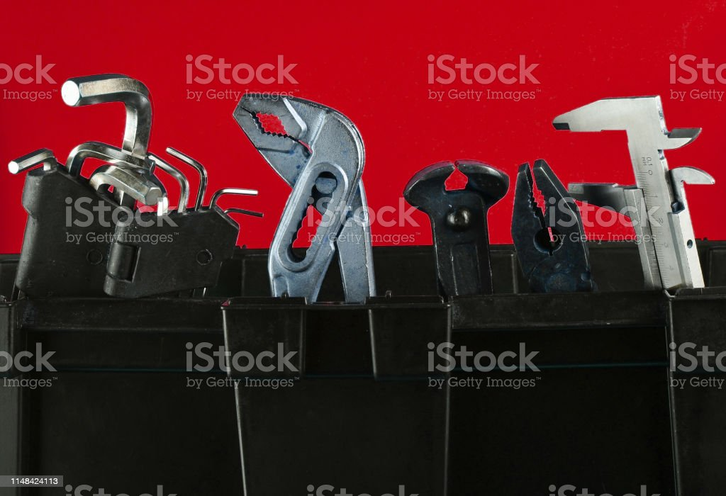 Garage plastic tool box with working tools isolated on red. Nippers,...
