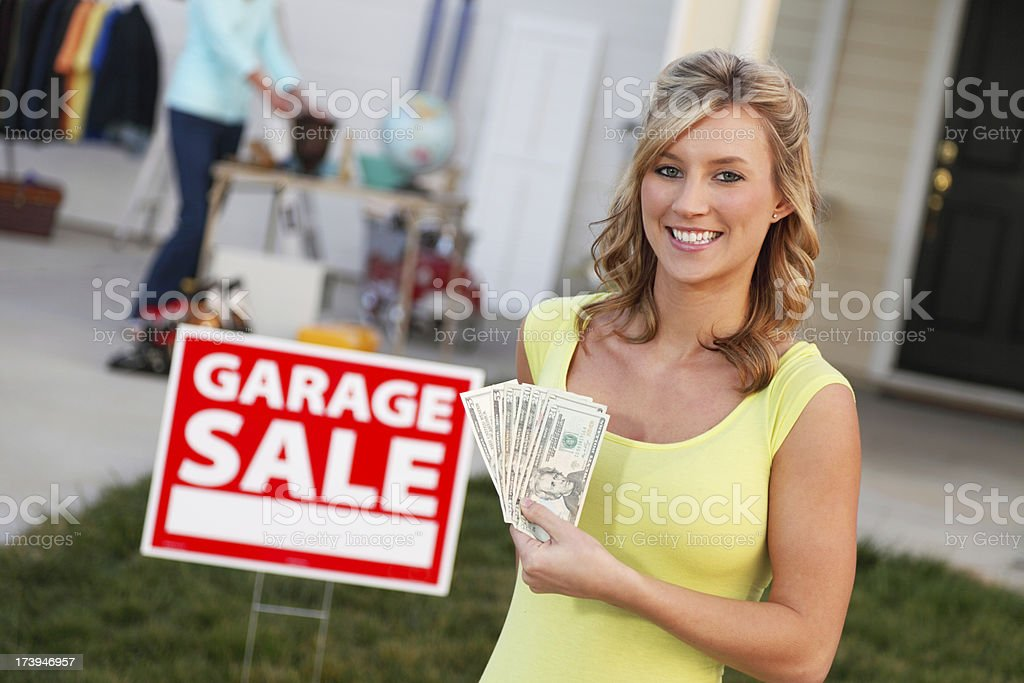 Homeowner holding money made at a Garage Sale.
