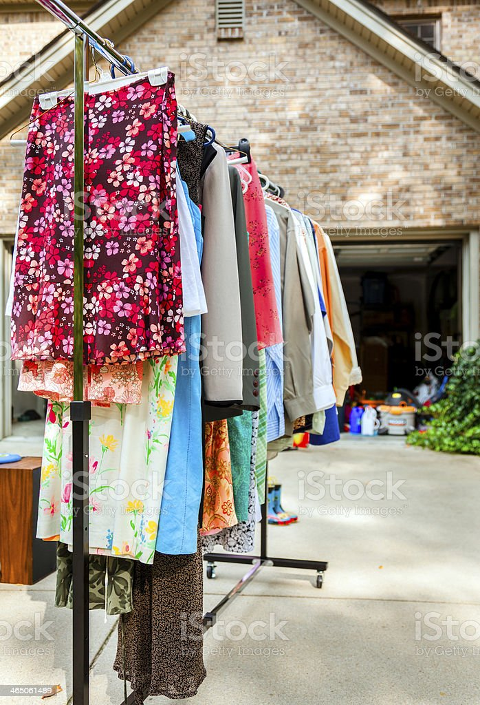 Image of clothes on hangers at a garage sale