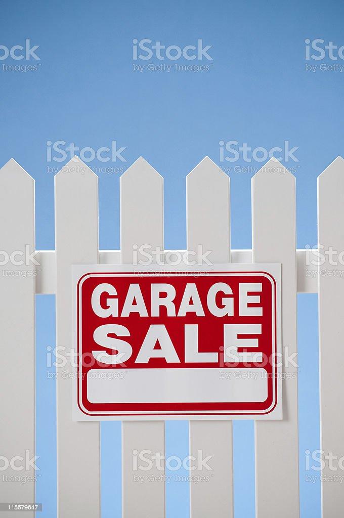Garage sale sign on white picket fence against blue sky.*
