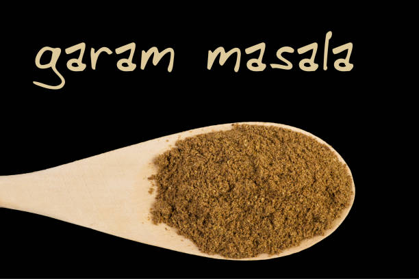 garam masala on wooden spoon isolated on black background garam masala on wooden spoon isolated on black background garam masala stock pictures, royalty-free photos & images