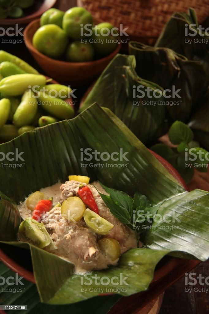 Garang Asem Ayam, the Javanese Dish of Tangy Chicken Curry in Banana Leaf Pouch stock photo