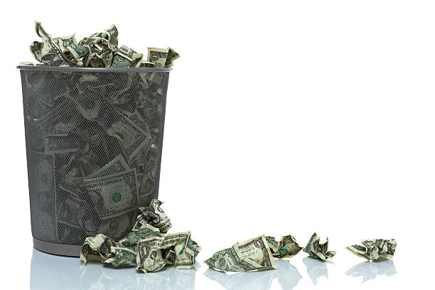Garbage can full of money spilling over Garbage can full of money spilling over, left side money to burn stock pictures, royalty-free photos & images