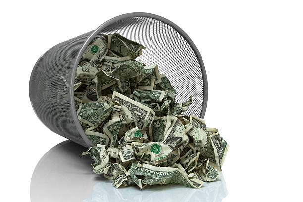 Garbage can full of money tipped on its side Garbage can full of money tipped on its side money to burn stock pictures, royalty-free photos & images