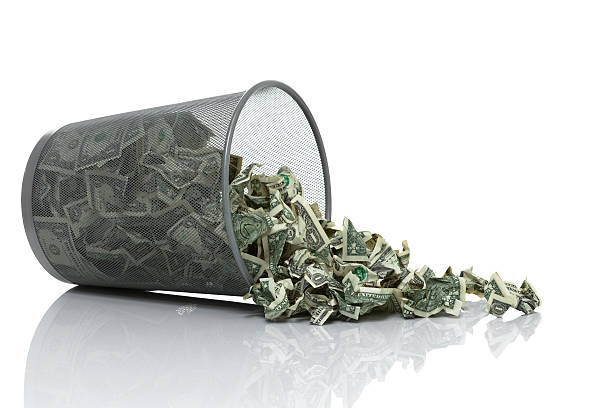 Garbage can full of money tipped on side spilling money Garbage can full of money tipped on its side with money spilling out money to burn stock pictures, royalty-free photos & images