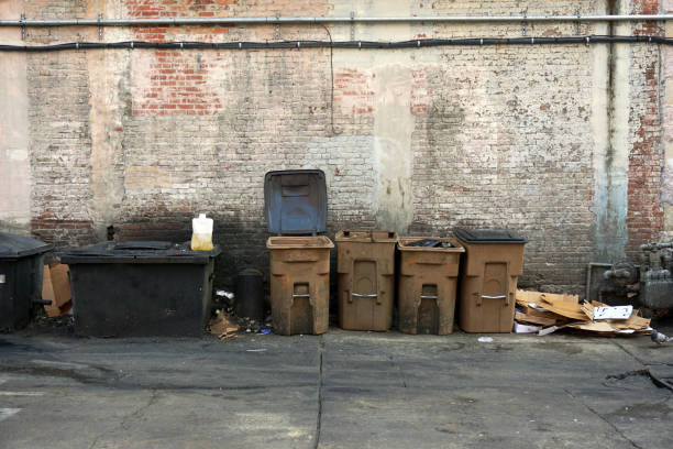 Garbage cans and assorted trash litter an alley. stock photo
