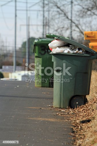 Garbage cans lined-up along a road ready to pick-up.