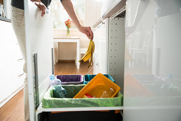 Garbage cans. Recycling concept. Woman putting banana peel in recycling bio bin in the kitchen cabinet. Person in the house separating waste. Different trash can with colorful garbage bags. apart stock pictures, royalty-free photos & images