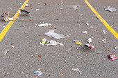 Saint Jon, NB, Canada - March 7, 2020: Garbage blows in the wind in a parking lot. A variety of garbage is present. Focus in the middle.