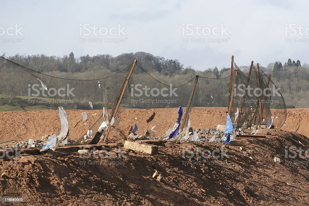 Garbage landfill site netting catching plastic rubbish bags in wind royalty-free stock photo