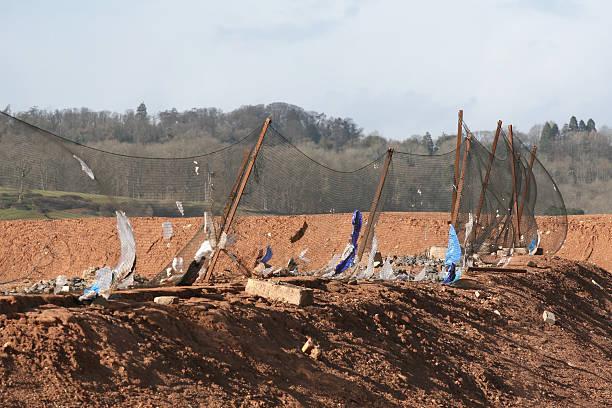 müll deponie website netzgewebe fangen kunststoff müll-taschen im wind - windbeutel stock-fotos und bilder