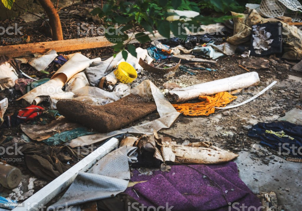 Garbage lying on the ground. Old rags, felt boots, plastic, glass, paper. stock photo