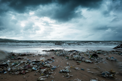 Garbage on beach, environmental pollution in Bali Indonesia. Storm is coming. And drops of water are on camera lens