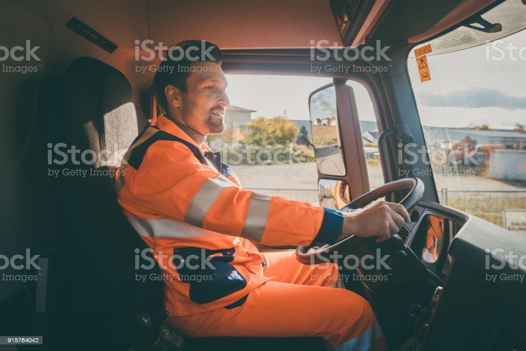 Garbage removal worker driving a dump truck stock photo