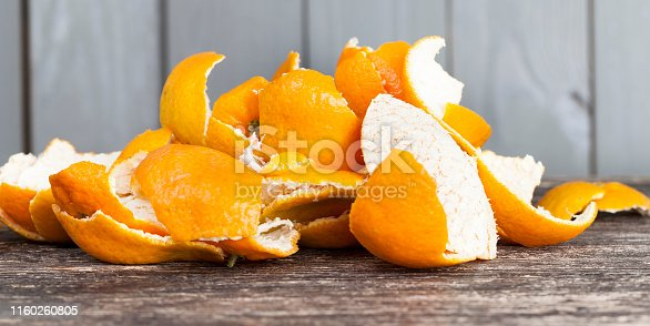 peel from tangerines peeled on a wooden table, orange peel to throw in the trash