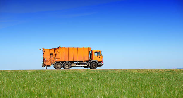 Garbage truck drives on country road through fields stock photo