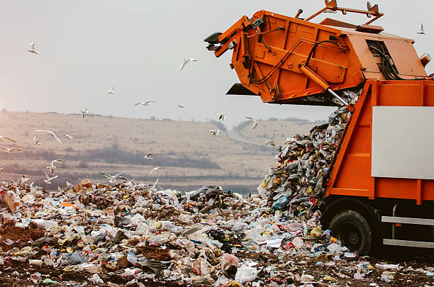 Garbage truck dumping the garbage Garbage truck dumping the garbage on a landfill  plastic pollution stock pictures, royalty-free photos & images