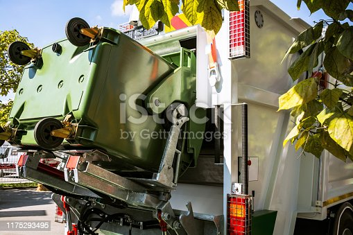 Public utility service - the garbage truck lifting a disposal container collecting trash