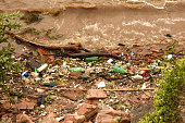 garbage washed ashore in filthy overflowing river