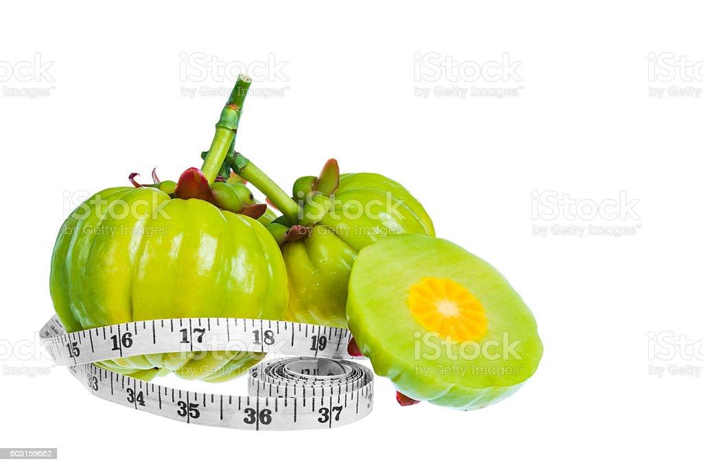 Garcinia cambogia fresh fruit with tapeline, isolated on white. stock photo