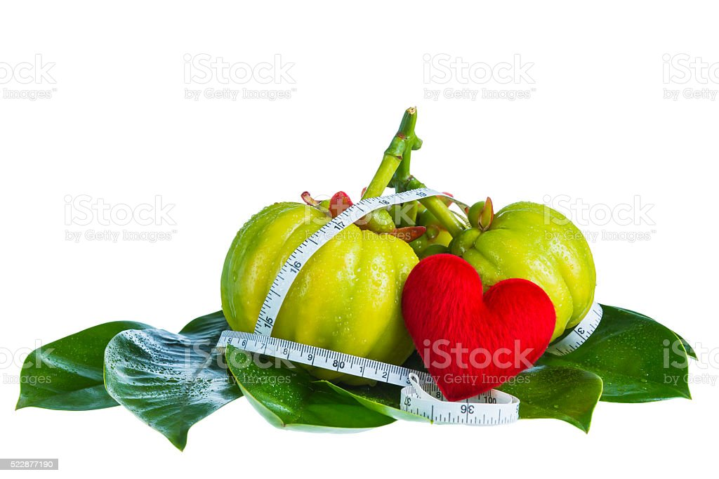 Garcinia cambogia with measuring tape, isolated on white backgro stock photo