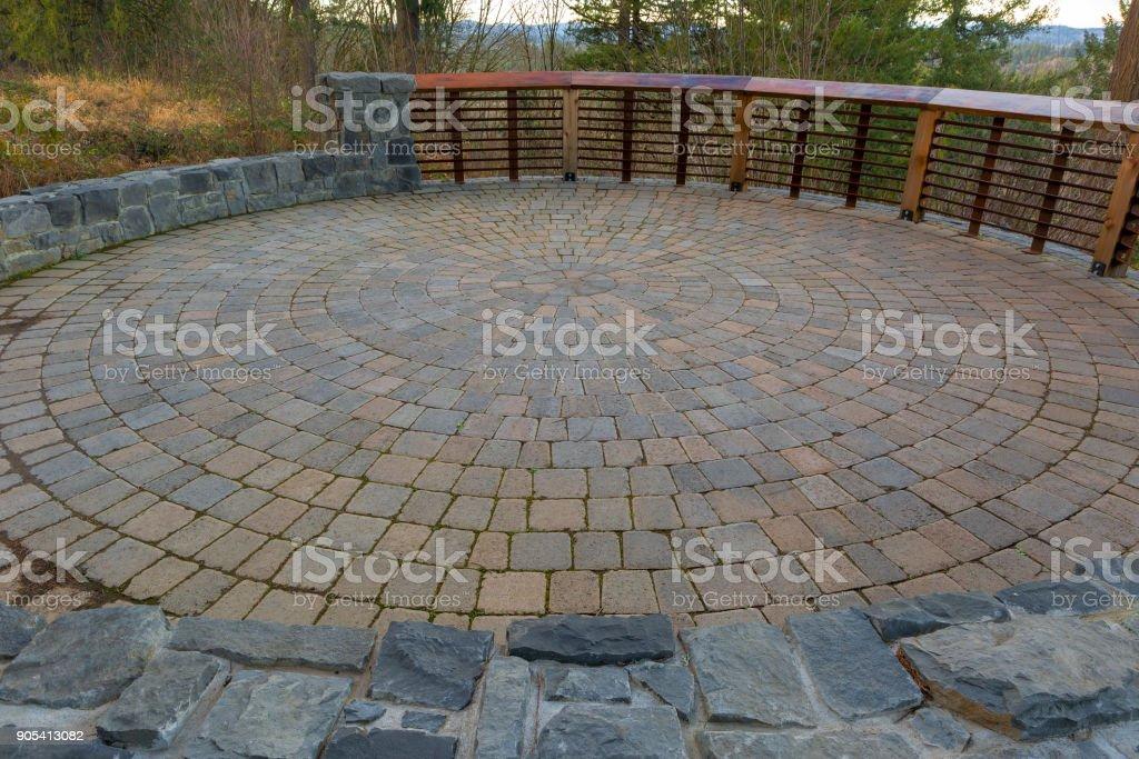Garden Backyard circular brick stone pavers hardscape patio with wood railings stone wall landscaping stock photo