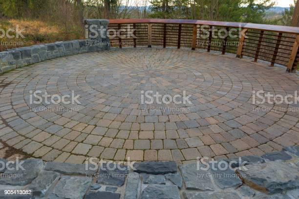 Photo of Garden Backyard circular brick stone pavers hardscape patio with wood railings stone wall landscaping