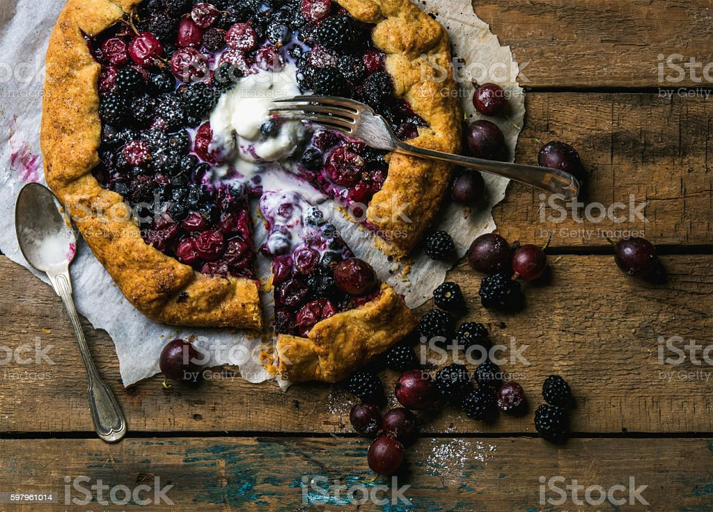 Garden berry crostata sweet pie with melted vanilla ice-cream stock photo