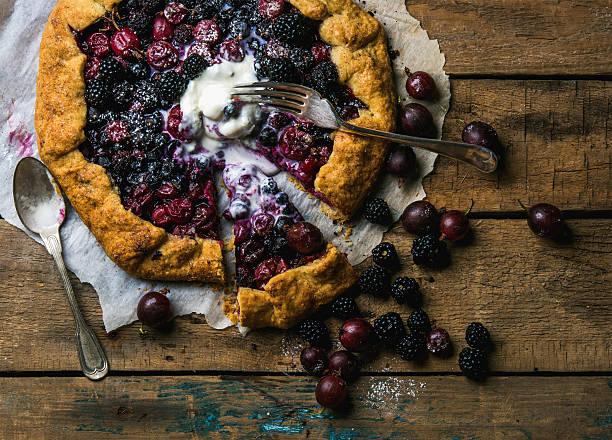 garden berry crostata sweet pie with melted vanilla ice-cream - crostata stock-fotos und bilder