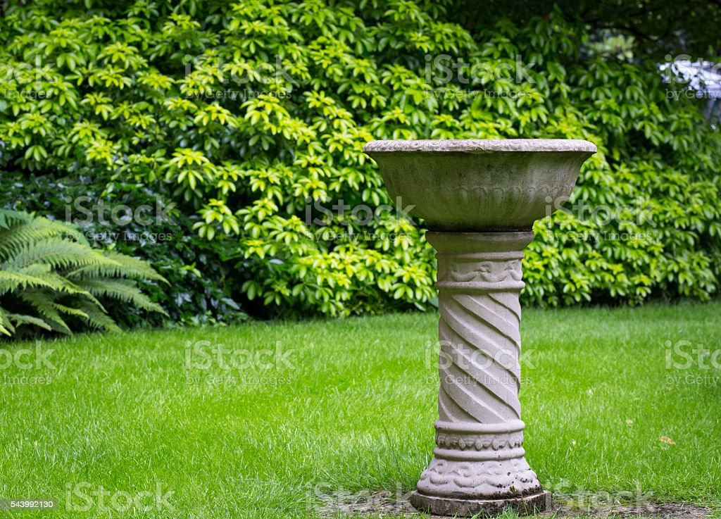 Garden bird concrete stone fountain stock photo