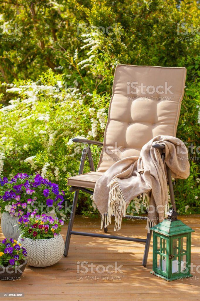 garden chair on terrace in sunlight, flowers  bush stock photo