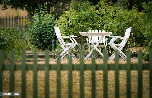 istock Garden chairs and table behind fence. Green grass and trees. Sweden, Europe, Scandinavia. 859852056