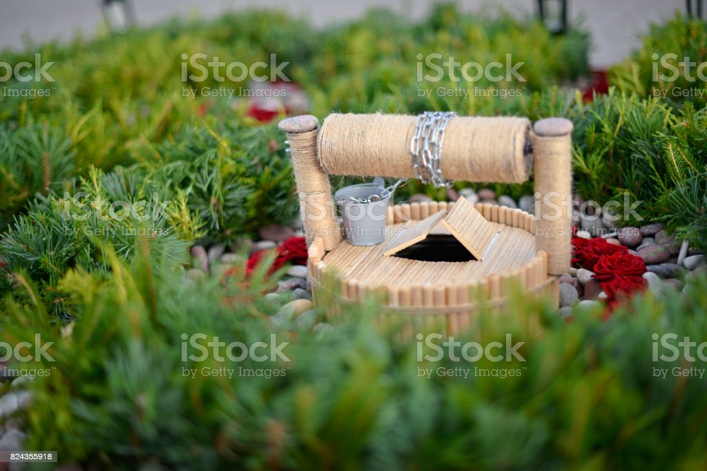 Garden composition of flowers and stones with a miniature well stock photo