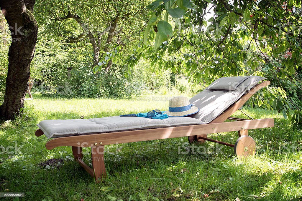 garden daybed of wood on a sunny meadow between trees stock photo