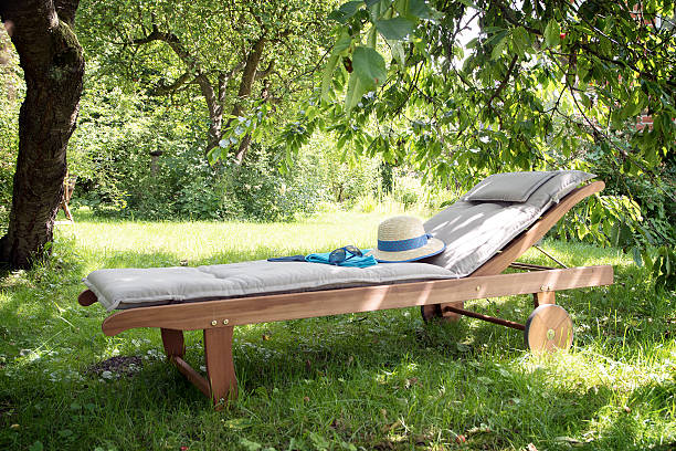 garden daybed of wood on a sunny meadow between trees - sun chair stock-fotos und bilder