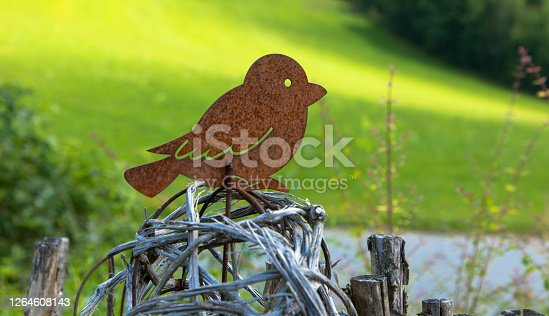 Garden decoration. A bird made of rusty sheet steel sits on a wooden fence. Space for text