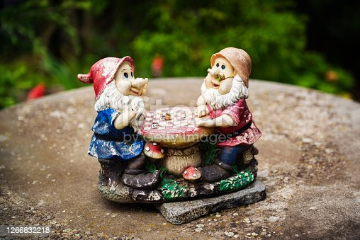 Two garden gnomes sit on a stone and play chess